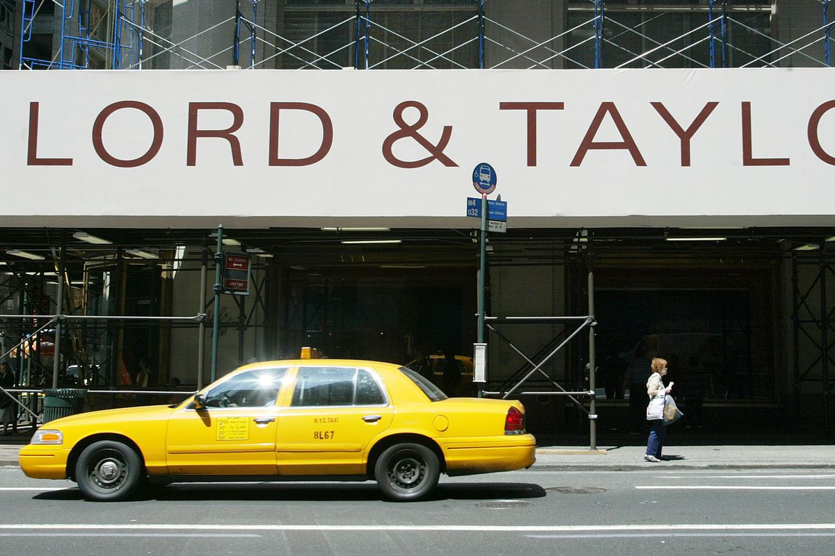 A yellow taxi outside of a Lord & Taylor store.