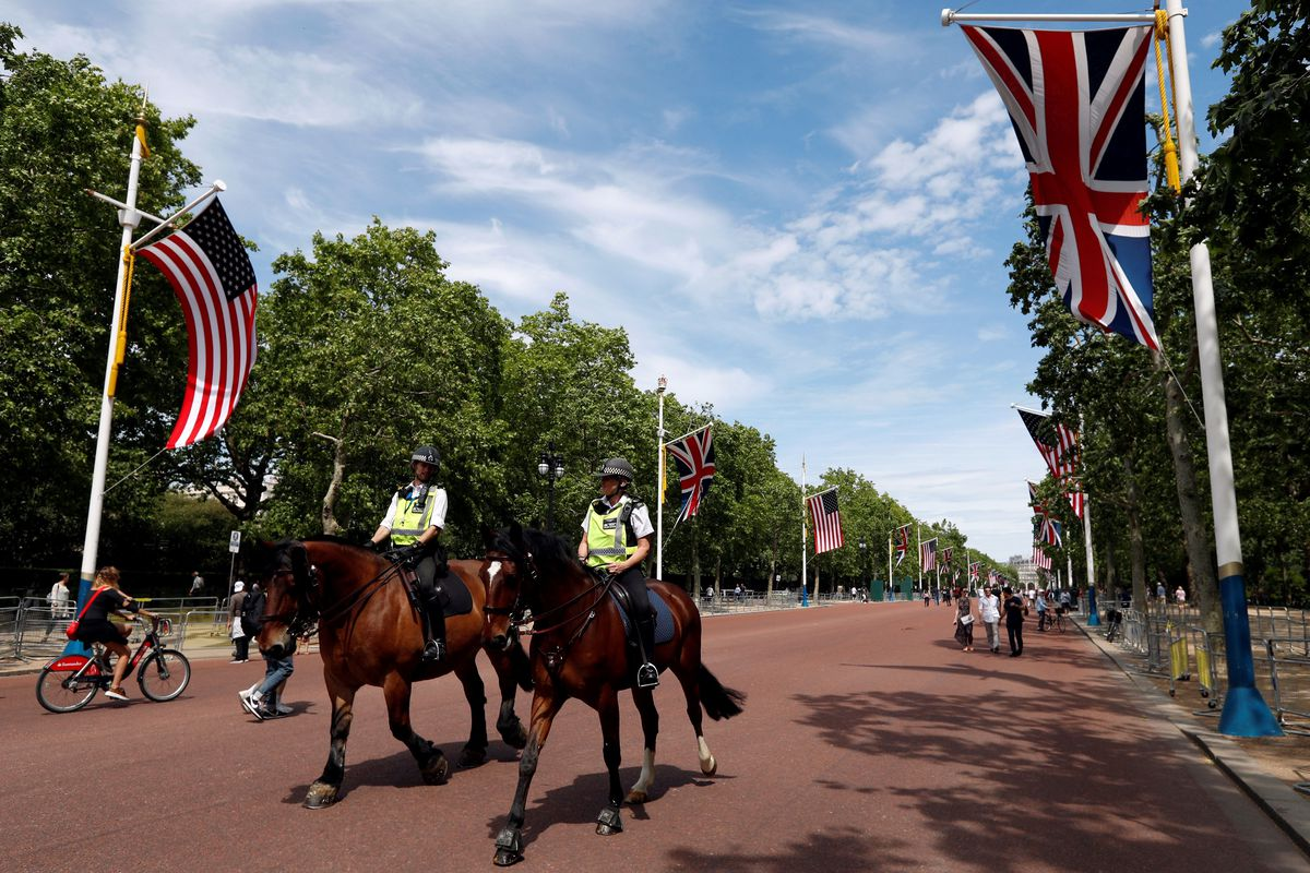 UK and US flags fly as police officers on horseback prepare for Trump's state visit.