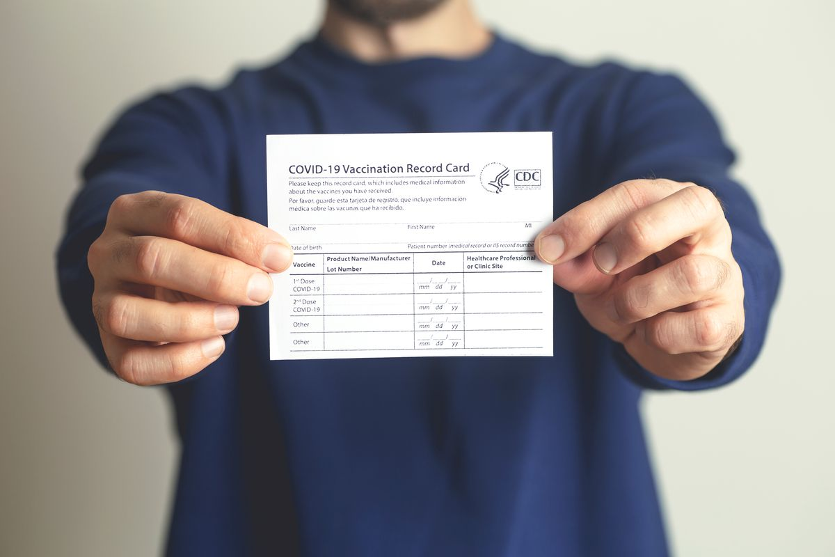 A man holds up a COVID vaccination card