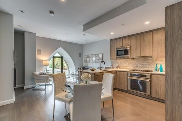 An open kitchen-dining room area with a triangular-shaped large window.