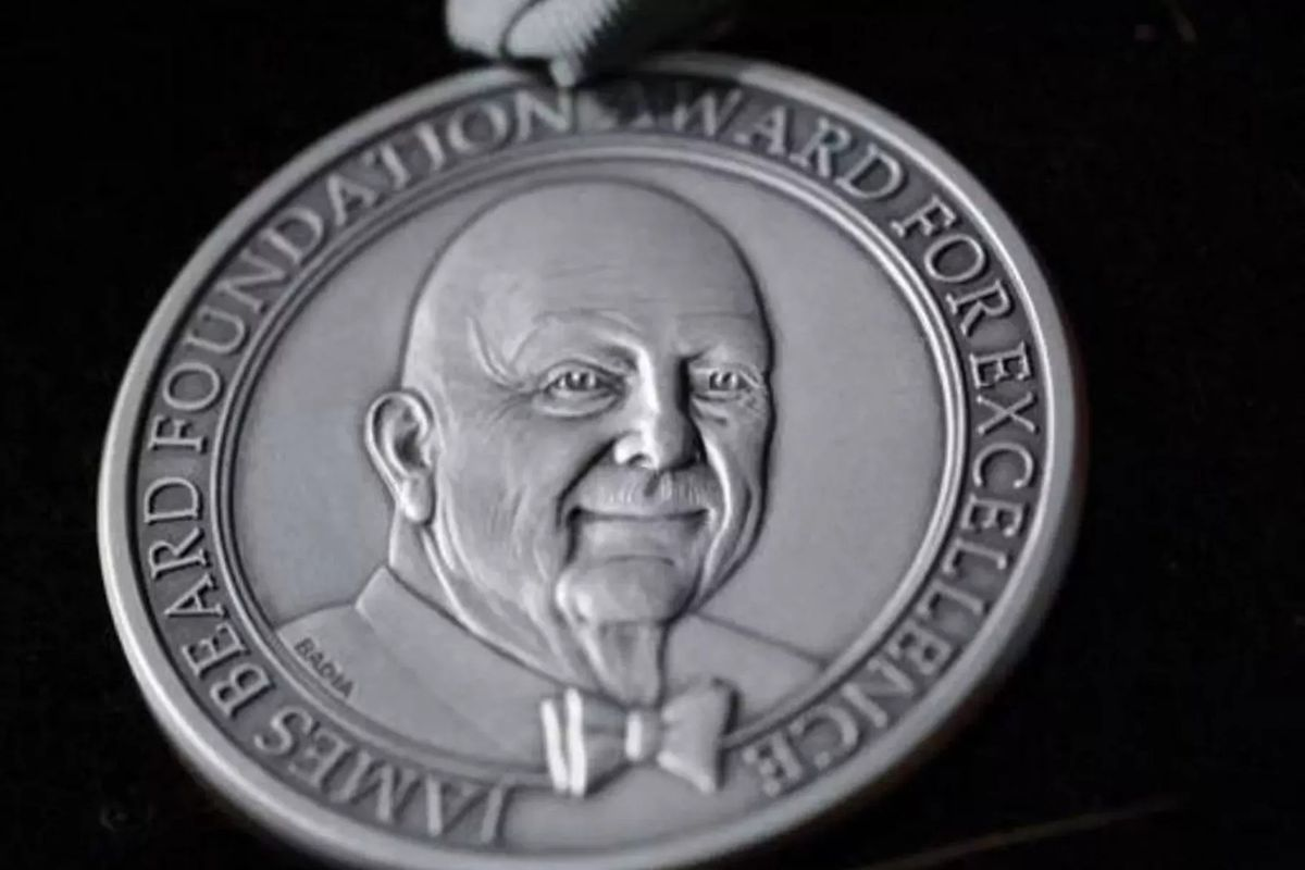 A silver James Beard Awards medal on a black background.