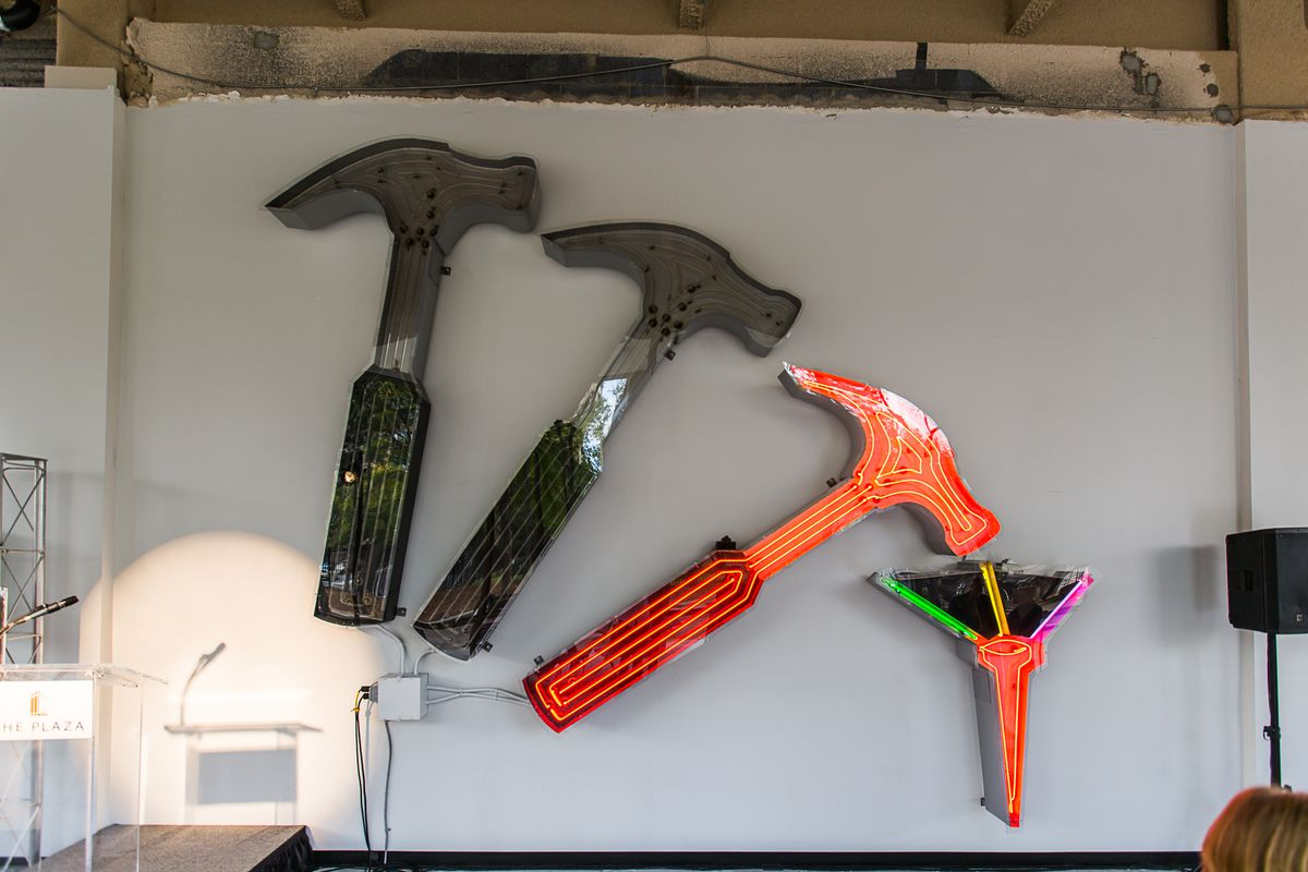 A hammer and nail sign with the third hammer and the nail's neon lit up, hangs on a wall on the ground floor of the Plaza.