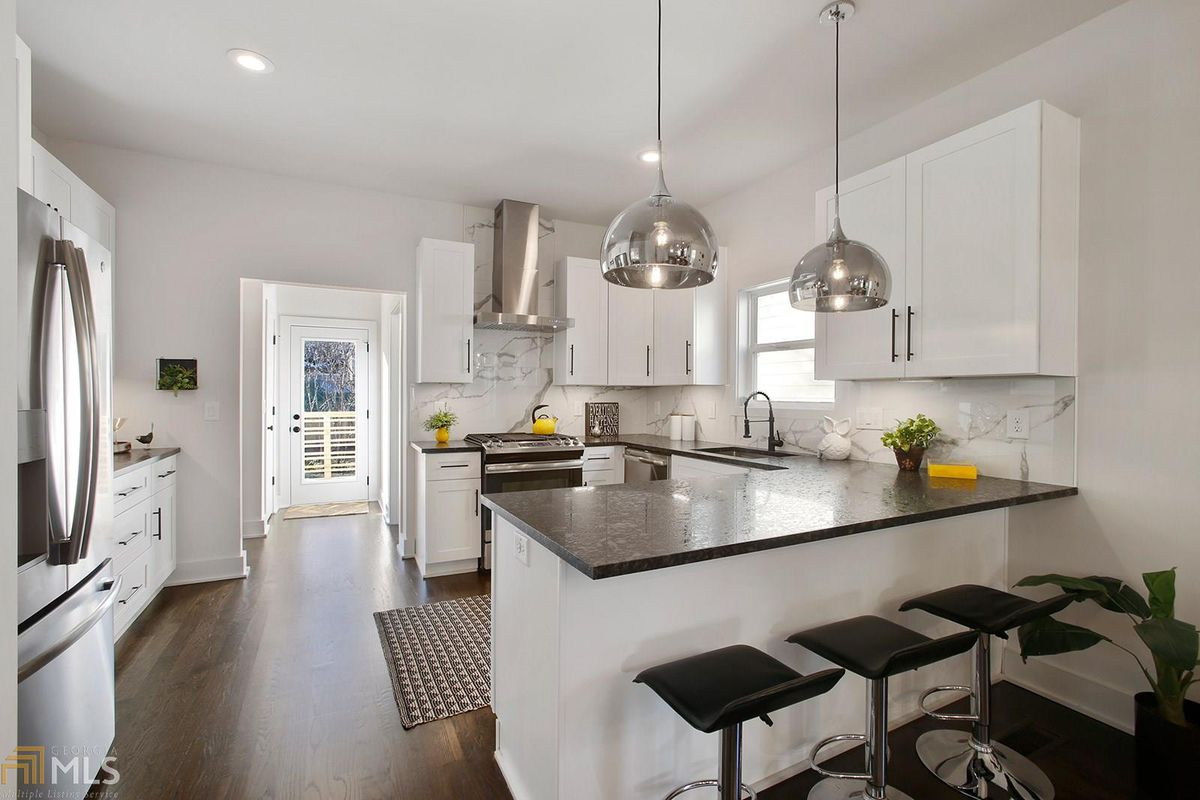 White kitchen with black countertops and black stools at the counter.