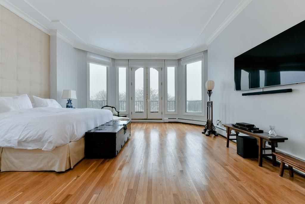 A large, airy bedroom with a bed and a bay window.