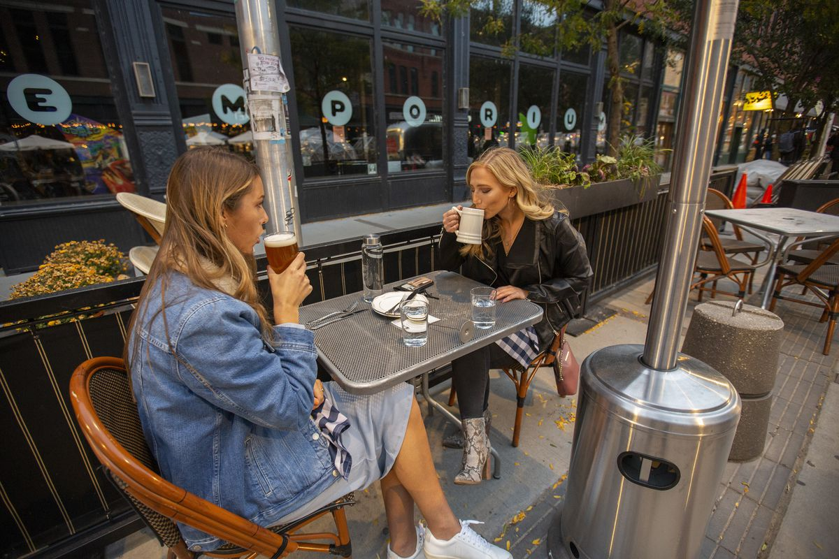 Two women sit at an outdoor table drinking beside a large patio heater