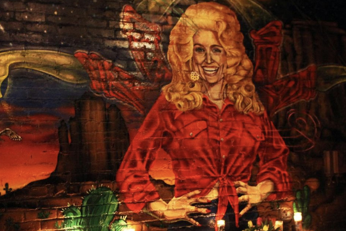 A Dolly Parton mural surrounded by candles