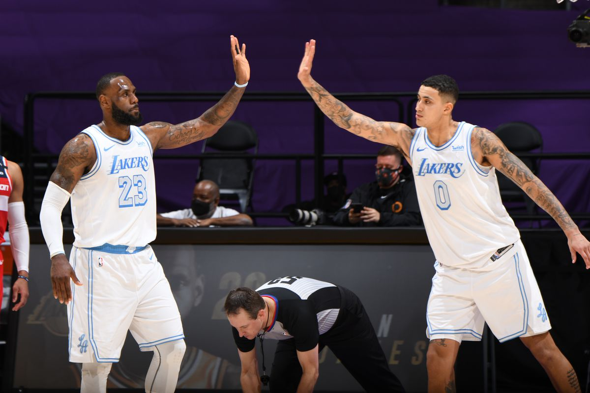 LeBron James of the Los Angeles Lakers high fives Kyle Kuzma of the Los Angeles Lakers during the game against the Washington Wizards on February 22, 2021 at STAPLES Center in Los Angeles, California.