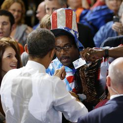 George Armour, right, flashes his GM identification badge as he greets President Barack Obama during a campaign event at Bowling Green State University, Wednesday, Sept. 26, 2012, in Bowling Green, Ohio.