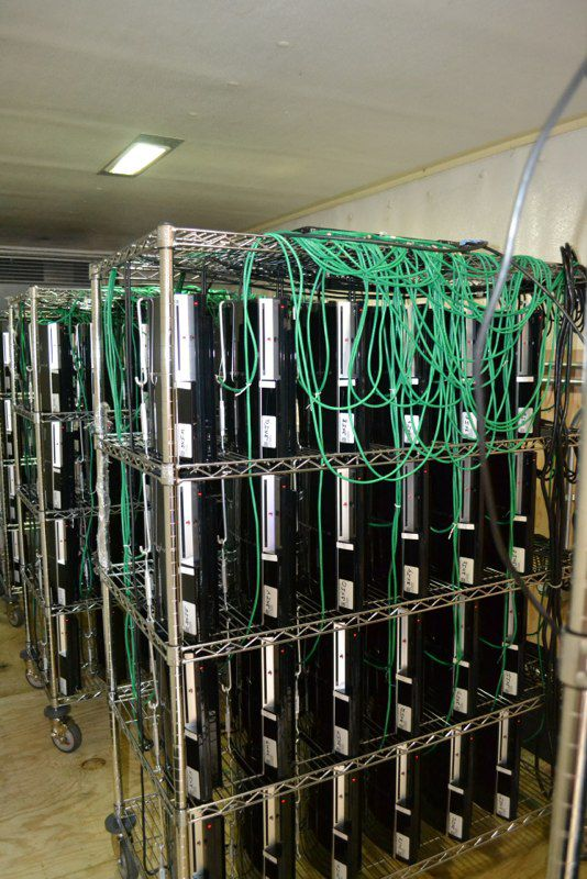 3 metal racks, each with 24 PS3s neatly arrayed on them in a room. the PS3s are connected with green wires