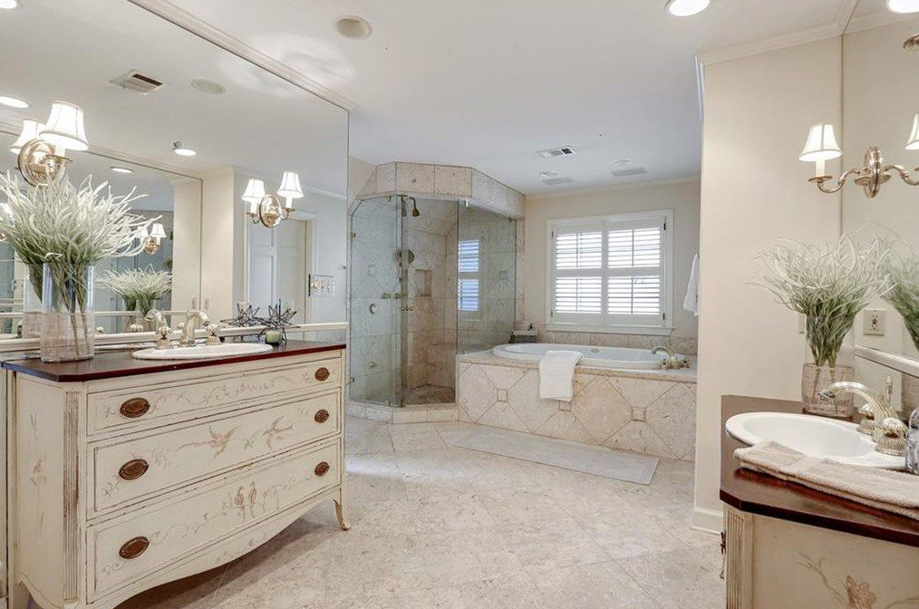 A white master bathroom with two vanities.