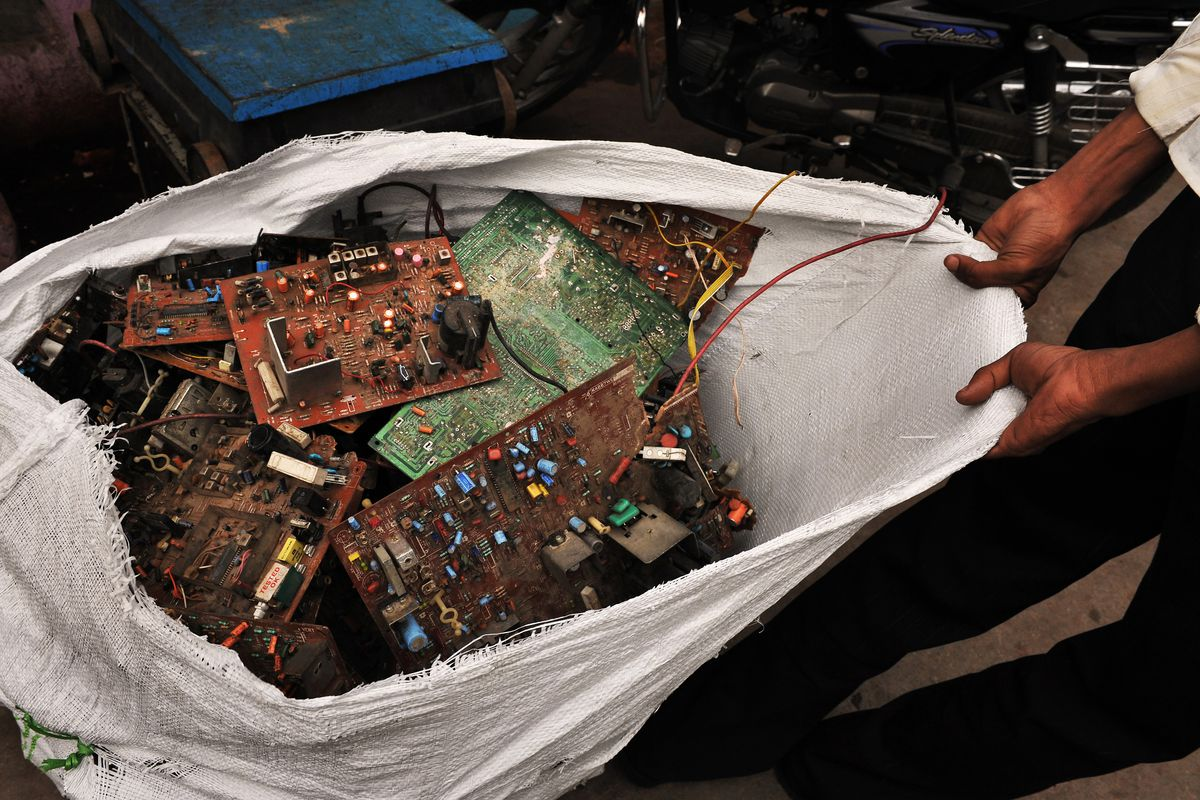 A laborer pulls a sackful of circuit boards