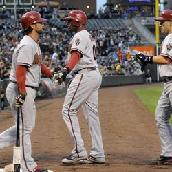 Arizona Diamondbacks' Ryan Roberts, left, congratulates Justin Upton, center, and Miguel Montero, right, after they scored on a Geoff Blum two-RBI single against the Colorado Rockies during the first inning of a baseball game on Friday, April 13, 2012, in Denver.
