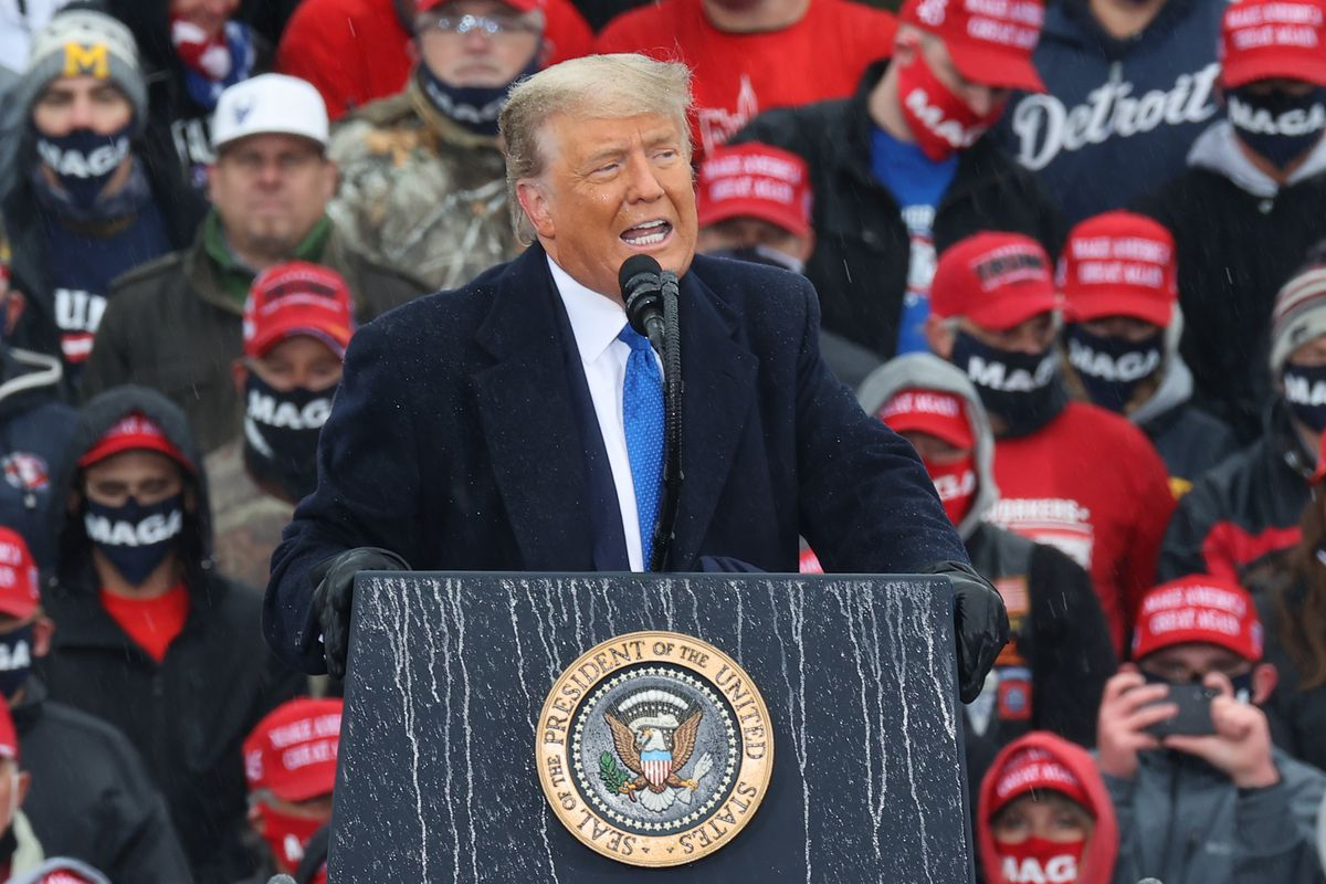 President Trump standing and talking from behind a podium, with people listening behind him.