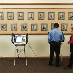 Brad Jones, left, gets help from voting judge Diane Wheeler in using an electronic voting machine in Farmington.