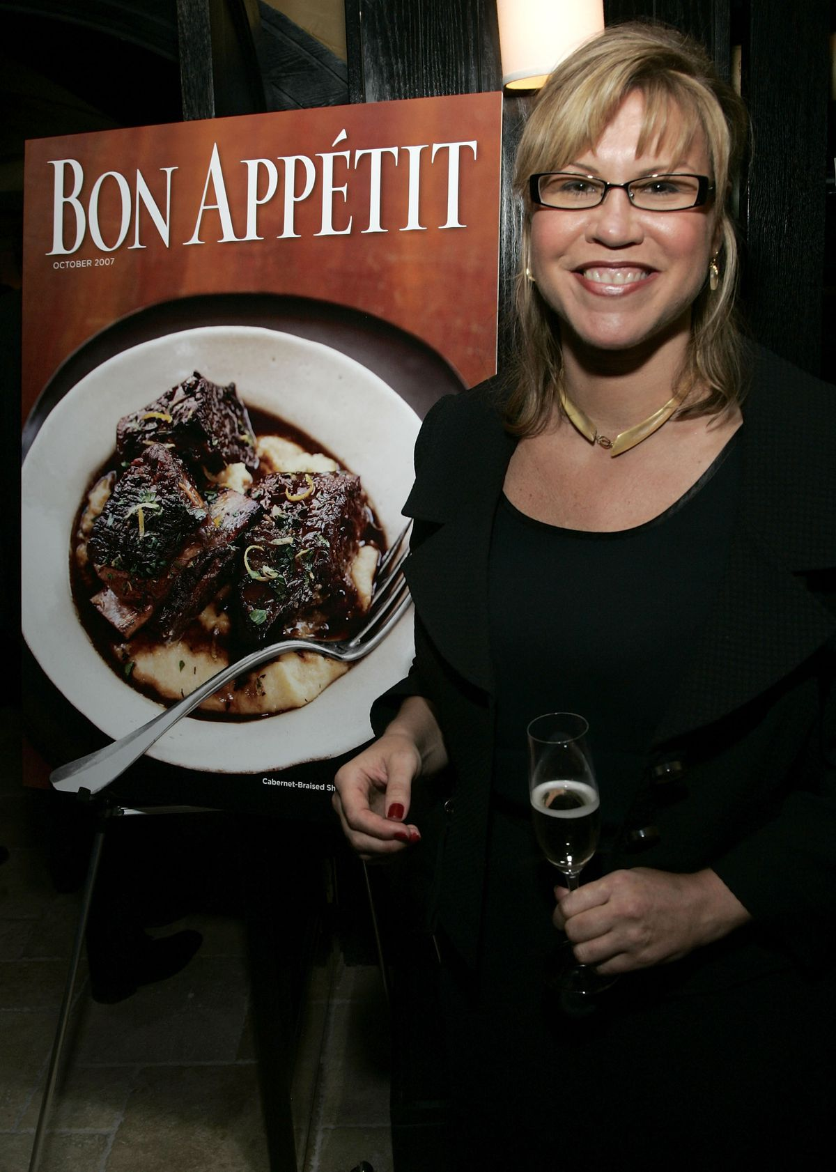 Audrey Saunders, with blonde hair and black-rimmed glasses, holds a Champagne flute in front of a Bon Appetit sign.
