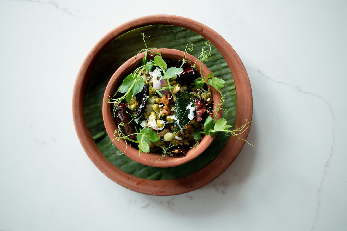 A red clay bowl filled with leafy sprouted legumes and other vegetables.