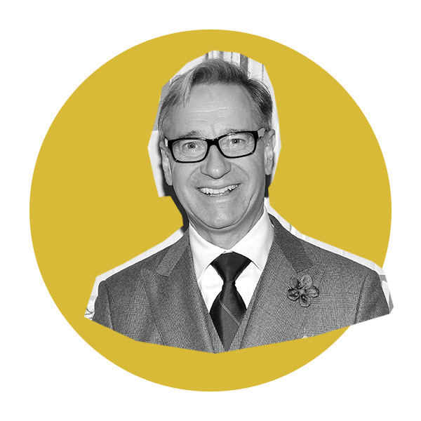 A black and white image of director Paul Feig in black, square-rimmed glasses, wearing a three-piece suit and tie.