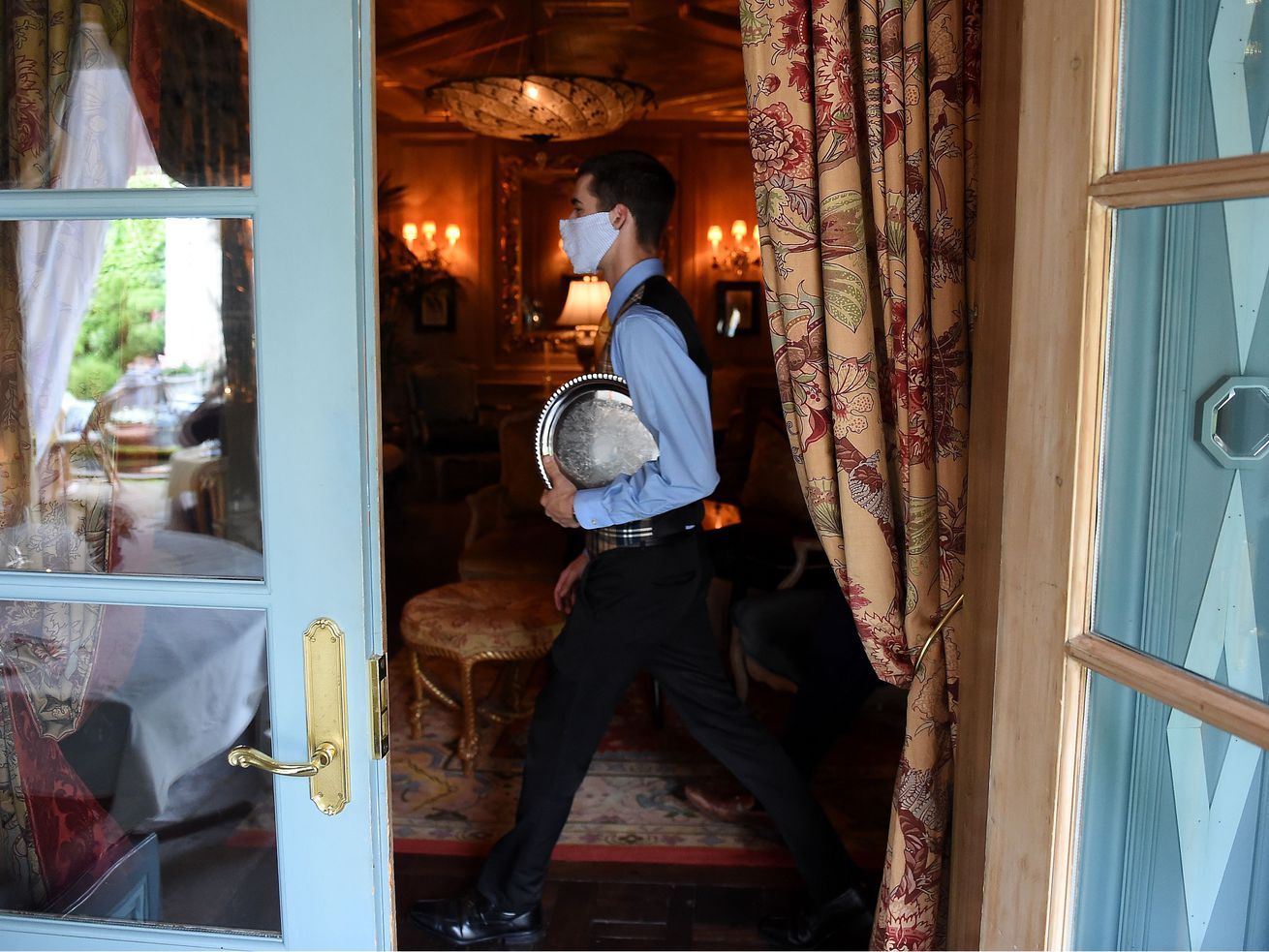 A waiter from The Inn at Little Washington, one of the country's most renowned restaurants, is viewed through an open door wearing a face mask while carrying a silver tray through a fancy dining room.