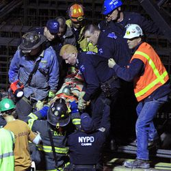 Emergency personnel remove an injured person from the site of a crane collapse where construction is going on for the 7 line subway extension Tuesday, April 3, 2012, in New York. Fire officials say the collapse at a Manhattan construction site injured two people.