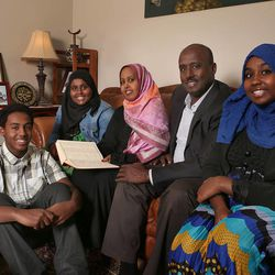 Aden Batar, surrounded by his wife, Asho Hamud, center, daughters Lail Batar, left, Ilham Batar, right, and son Ibrahim Batar, (two older sons not pictured), Bater was himself a Muslim refugee in Utah before becoming head of the refugee program for Catholic Community Services, Monday, Nov. 4, 2013, in West Valley City.