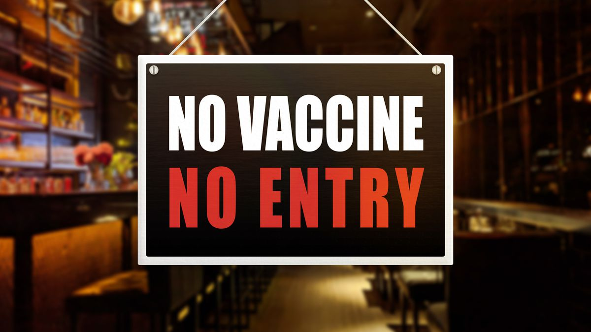 """A sign hung on a restaurant window reads """"No Vaccine No entry"""" in bold all-caps lettering."""