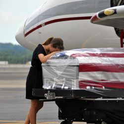 FILE - In this Thursday, May 3, 2012 photo provided by the Tennessee National Guard, Ashley Edens leans on the casket of her husband, Spc. Jason Edens, in Smyrna, Tenn. Spc. Edens was killed April 15, 2012 during combat in Afghanistan. Eleven years after the U.S. began battling to rid Afghanistan of al-Qaida and the Taliban, the war has ebbed from the headlines. The question of just how to end it is barely mentioned in the speeches of this year's presidential campaign. Polls find most Americans just want it over.