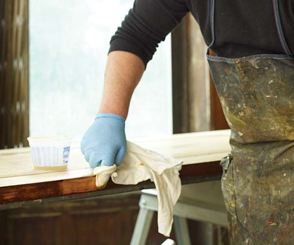 Person Stripping Paint Off Of Wood Furniture