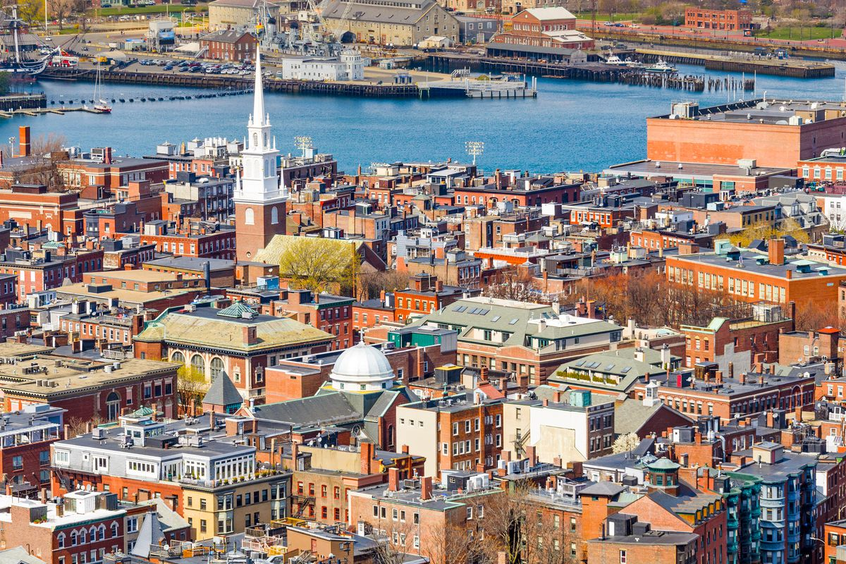 An 18th-century church's steeple prominent against an aerial shot of a cityscape.