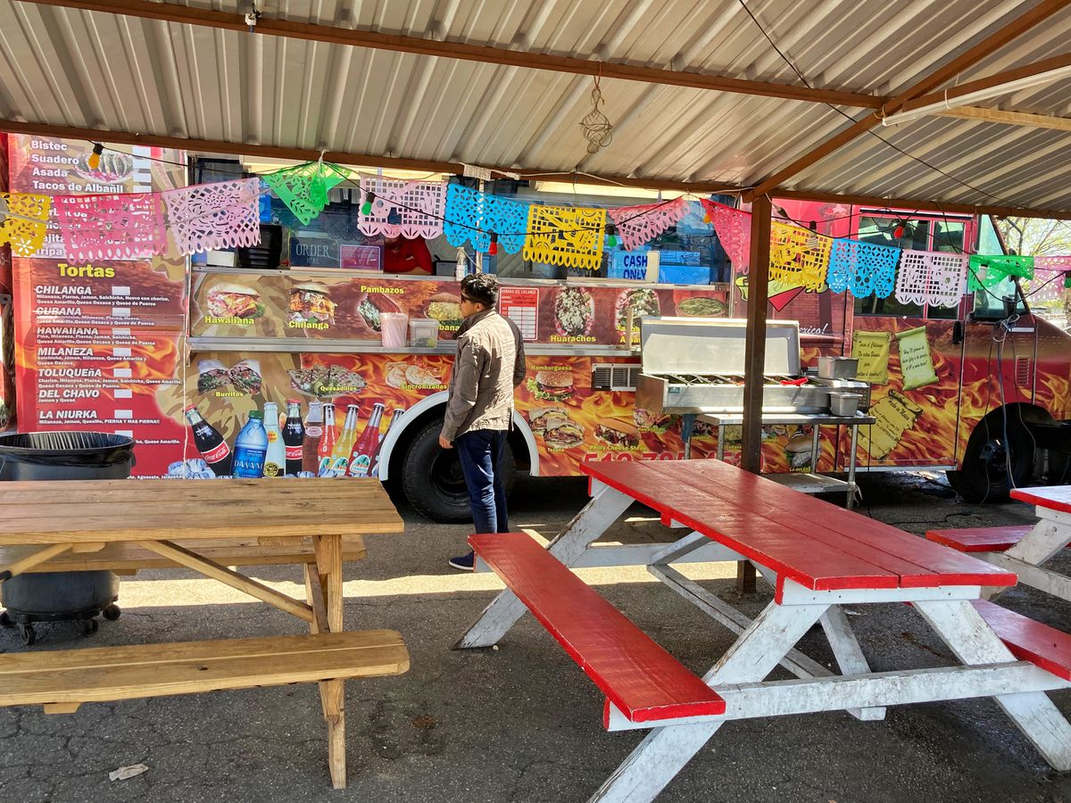 A man stands outside a food truck with a shade structure and picnic tables.