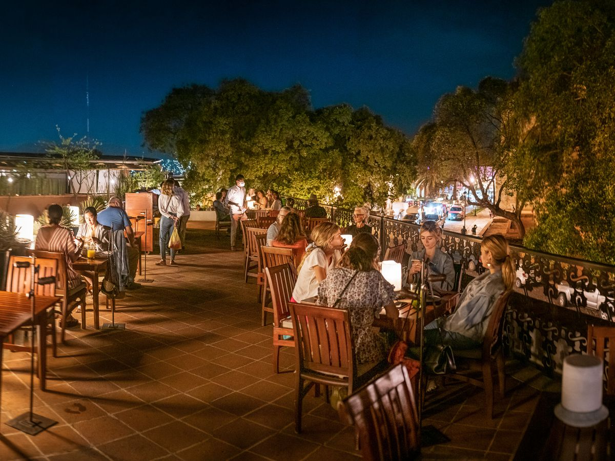 A nighttime scene on a patio with people at tables.