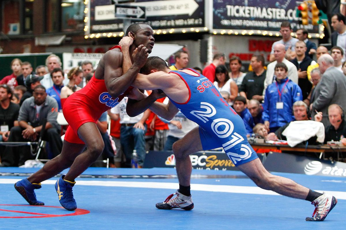 June 7, 2012; New York, NY, USA; Shawn Bunch (red) grabs Coleman Scott (blue) during the first bout of the 60kg mens freestyle match against at the U.S Olympic Team Wrestle-off at Duffy Square. Mandatory Credit: Debby Wong-US PRESSWIRE