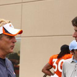 Broncos Defensive Coordinator Jack Del Rio (left) speaks with former Broncos WR Ed McCaffrey after practice.