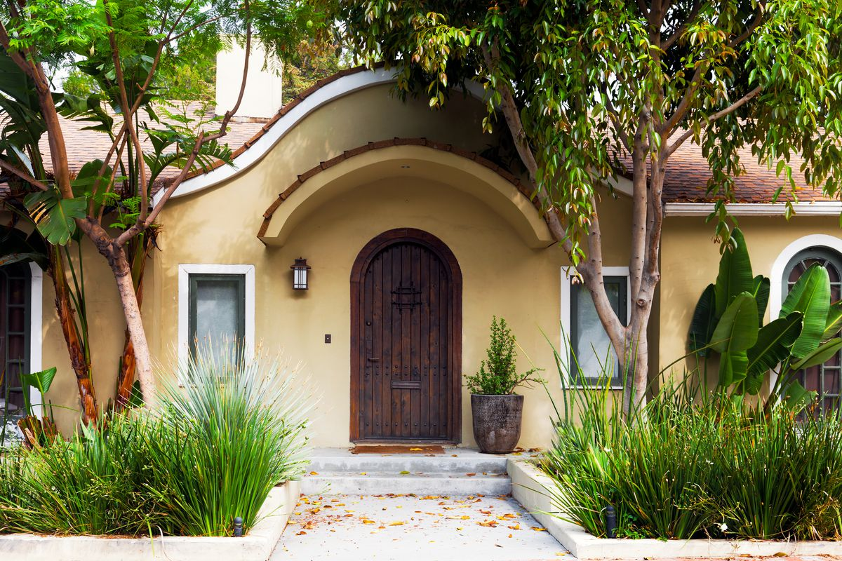 The front door of a home in LA, a rounded wooden doorway, tile roof, surrounded by plants and lush plants.