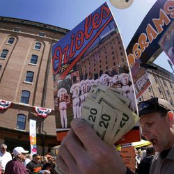 In this photograph shot with a fisheye lens, John Markiewicz sells programs before the Baltimore Orioles home opener baseball game against the Minnesota Twins in Baltimore, Friday, April 6, 2012.