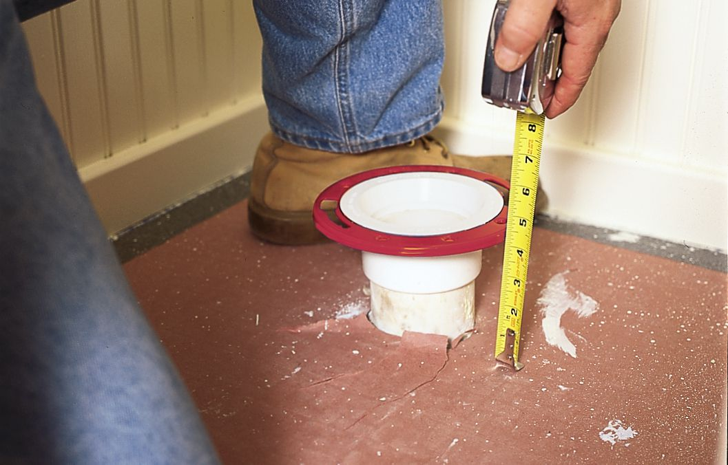Man Measures Gap Between Bottom Of Flange's Collar And Finish Floor To Install Toilet