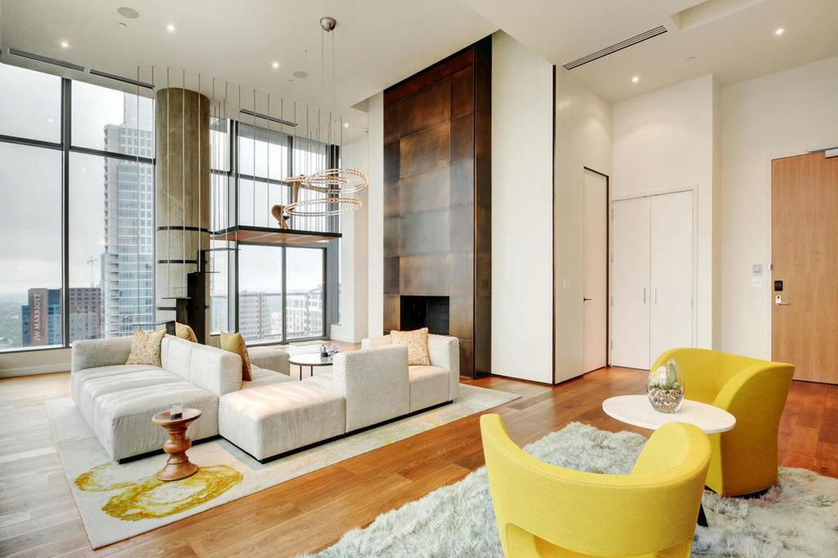 Two-story penthouse living room with large windows looking on to city