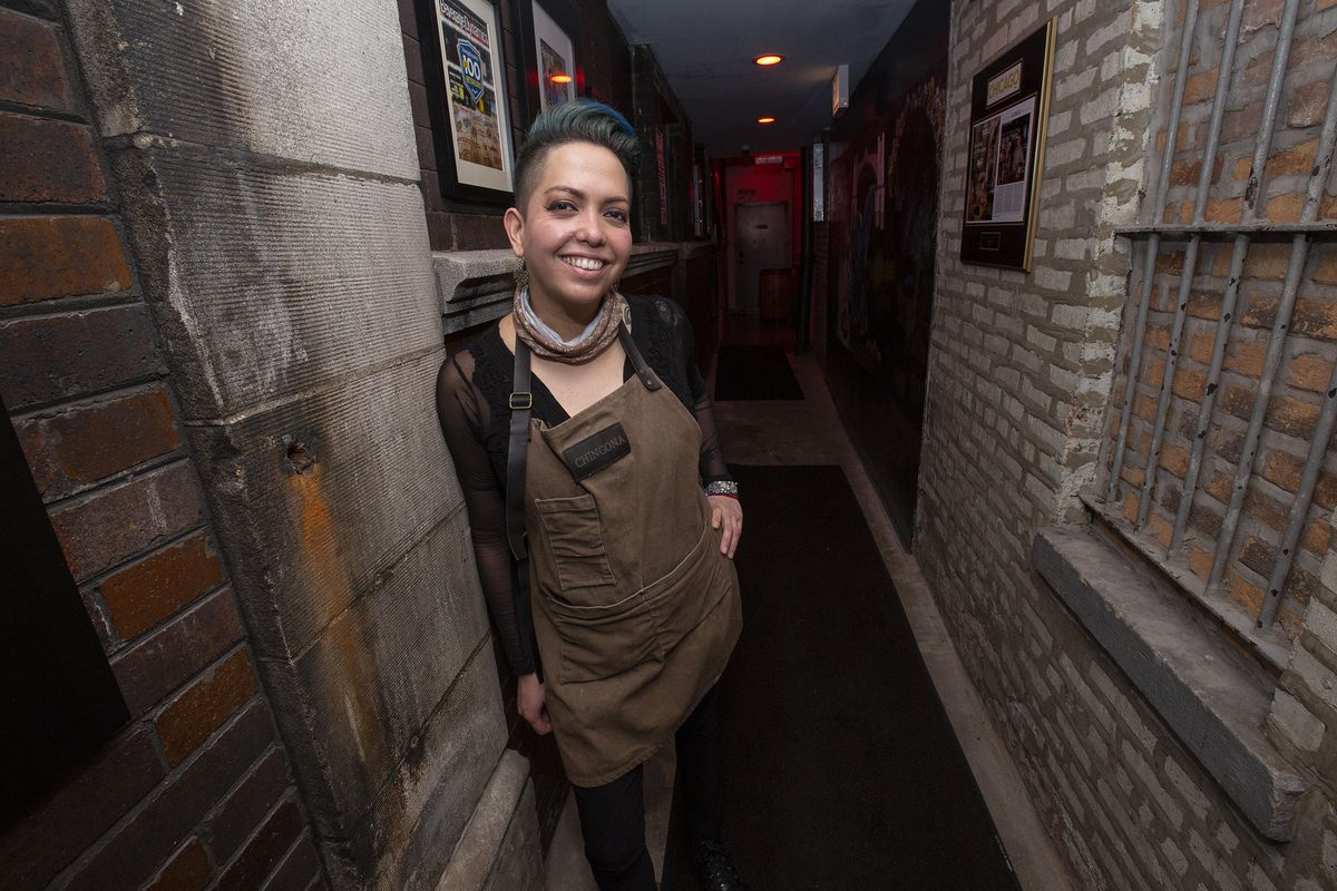 A smiling, blue-haried person with an apron standing in a brick alley.