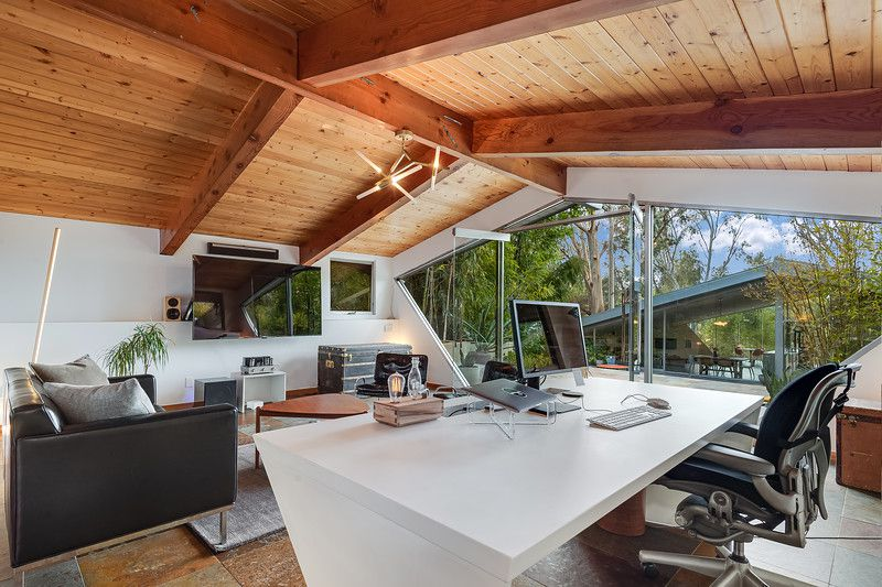 A home office with exposed beam ceilings and a wall of windows overlooking the main house.