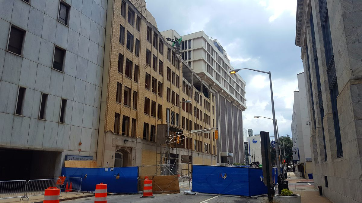 A construction photo showing the dismantling of a six-story building.