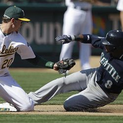 Seattle Mariners' Carlos Triunfel, right, slides safe at third base beneath the tag of Oakland Athletics third baseman Josh Donaldson in the fifth inning of a baseball game Saturday, Sept. 29, 2012, in Oakland, Calif. Triunfel advanced to third on a sacrifice fly hit by Franklin Gutierrez.