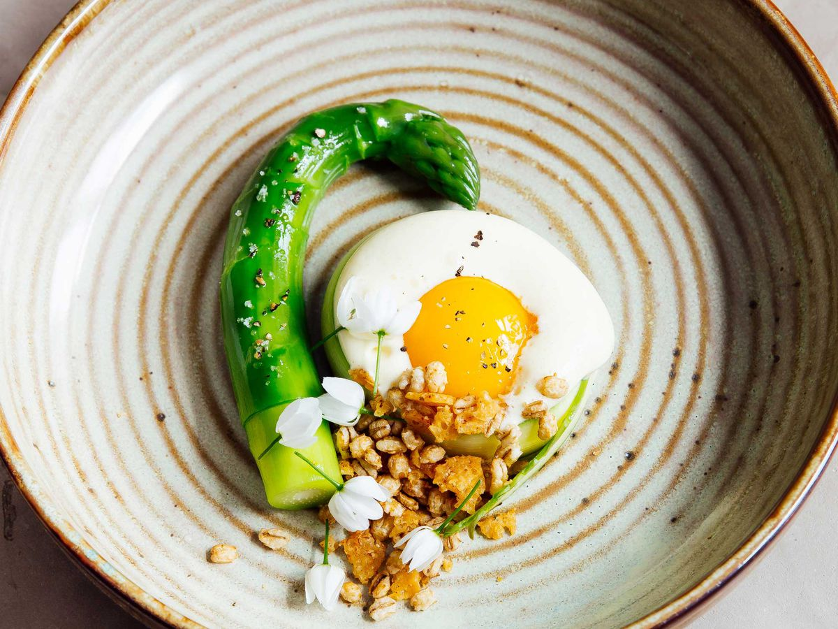 From above, a large stalk of asparagus curls around a sunny-side up egg garnished with seeds and flowers