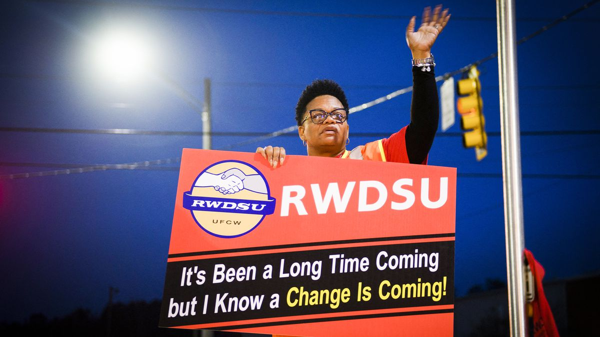 """A union organizer holds a sign that reads, """"RWDSU. It's been a long time coming but I know a change is coming!"""""""