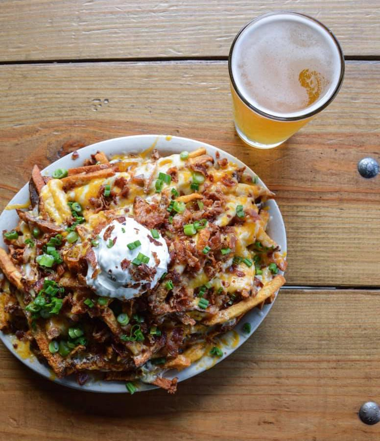 A pile of fries topped with cheese and herbs on a white plate next to a glass of beer on a table