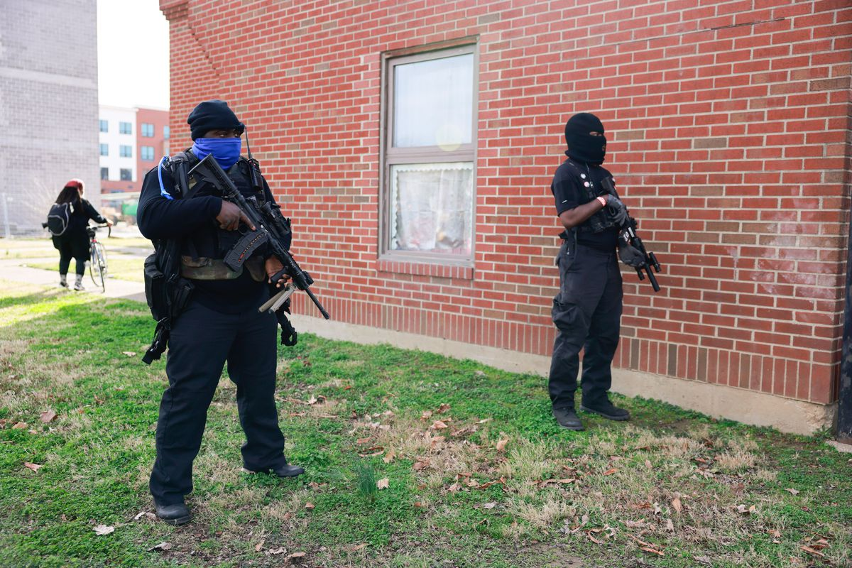 Police holding guns stand by a brick wall.