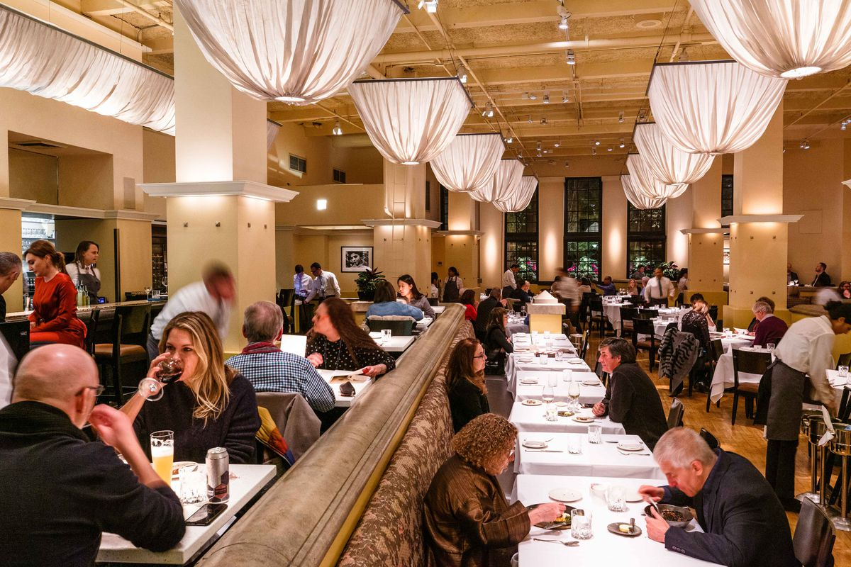 Puffy fabric chandeliers hang above the dining room at Gotham, while patrons dine at tables draped in white linens