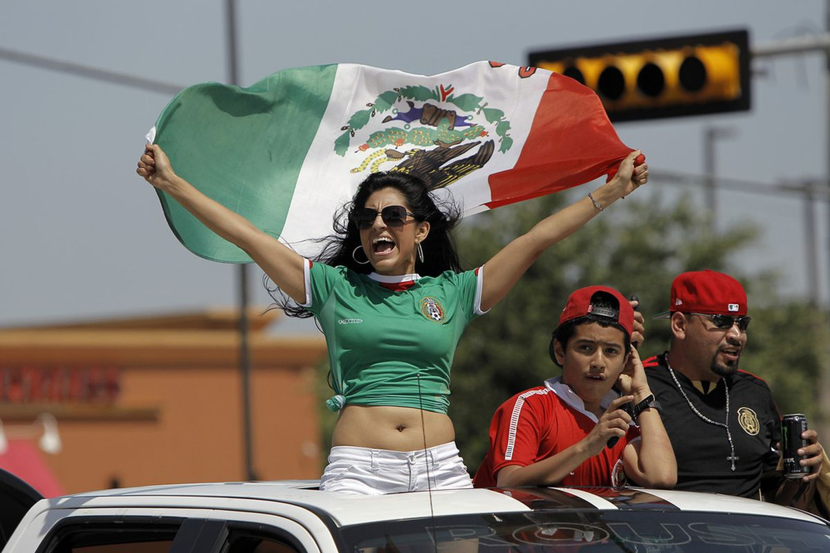 ARLINGTON, TX - JUNE 3: A Mexico soccer fan stands up through a sun roof of a car waving the Mexican flag before a soccer game against Brazil at Cowboys Stadium on June 3, 2012 in Arlington, Texas. (Photo by Brandon Wade/Getty Images)