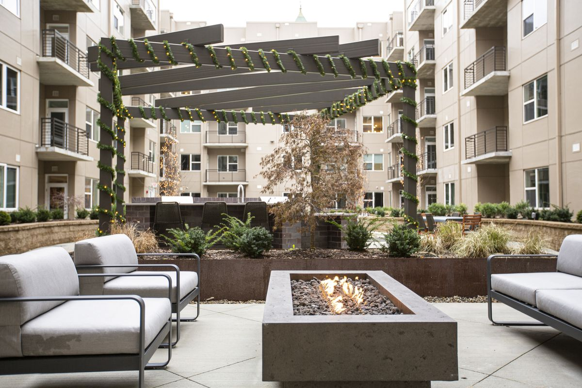 Couches on either side of a firepit next to a pergola. Apartments and balconies surround the courtyard.