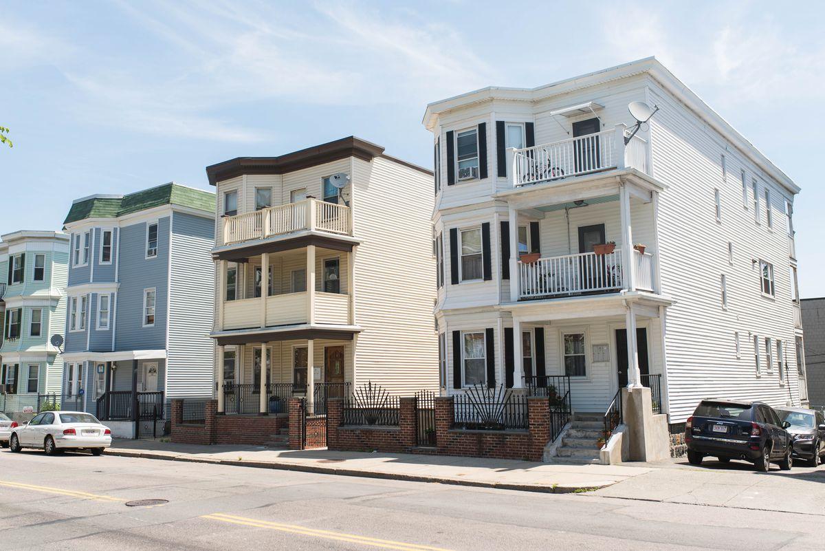 Triple-decker buildings in Boston. Each is three floors. The sidewalks in front are empty.
