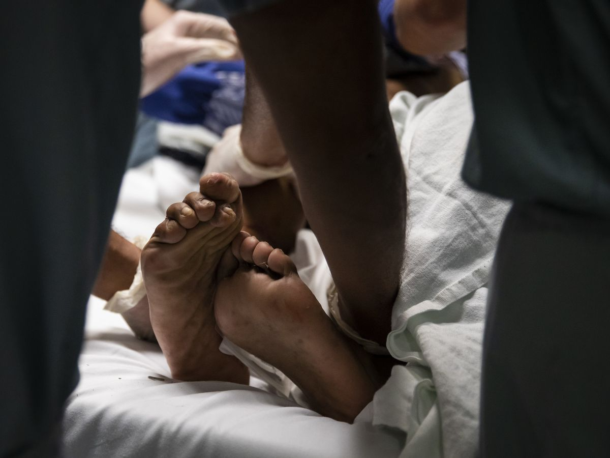 A man being seen for a stab wound curls his toes and writhes in pain at Mount Sinai Hospital.