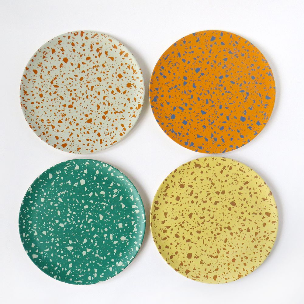 Four porcelain plates with different colored terrazzo patterns.